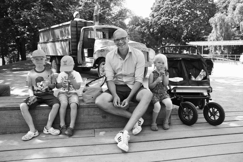 Siblings enjoy a lunch break with their father at a park in the Odenplan neighborhood of Stockholm.