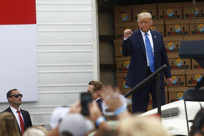 Trump stands in front of a truck full of food boxes.