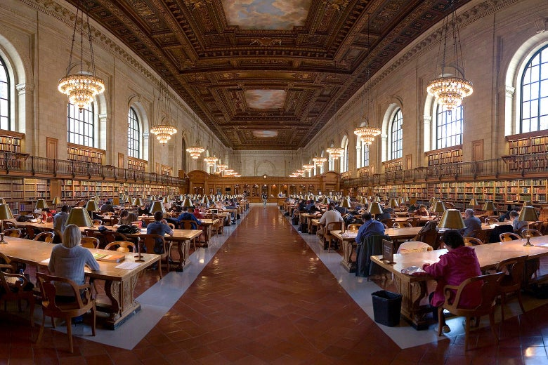 Patrons sit at long desks in an ornate reading room.