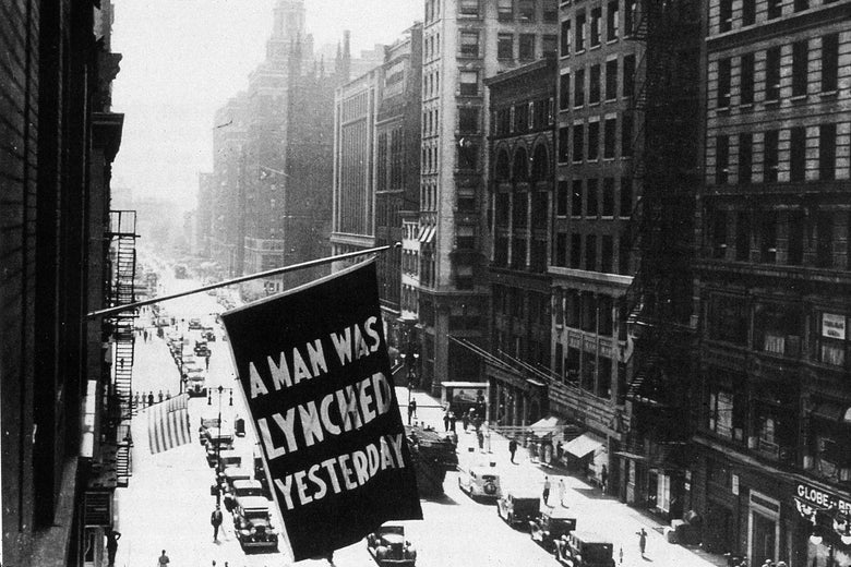 """A flag hanging outside the headquarters of the NAACP, bearing the words """"A Man Was Lynched Yesterday."""""""