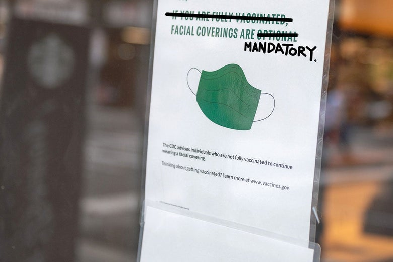 """A sign on a door reads, """"Facial Coverings Are Mandatory,"""" with """"If You Are Fully Vaccinated"""" and """"Optional"""" crossed out, and """"Mandatory"""" scrawled on."""