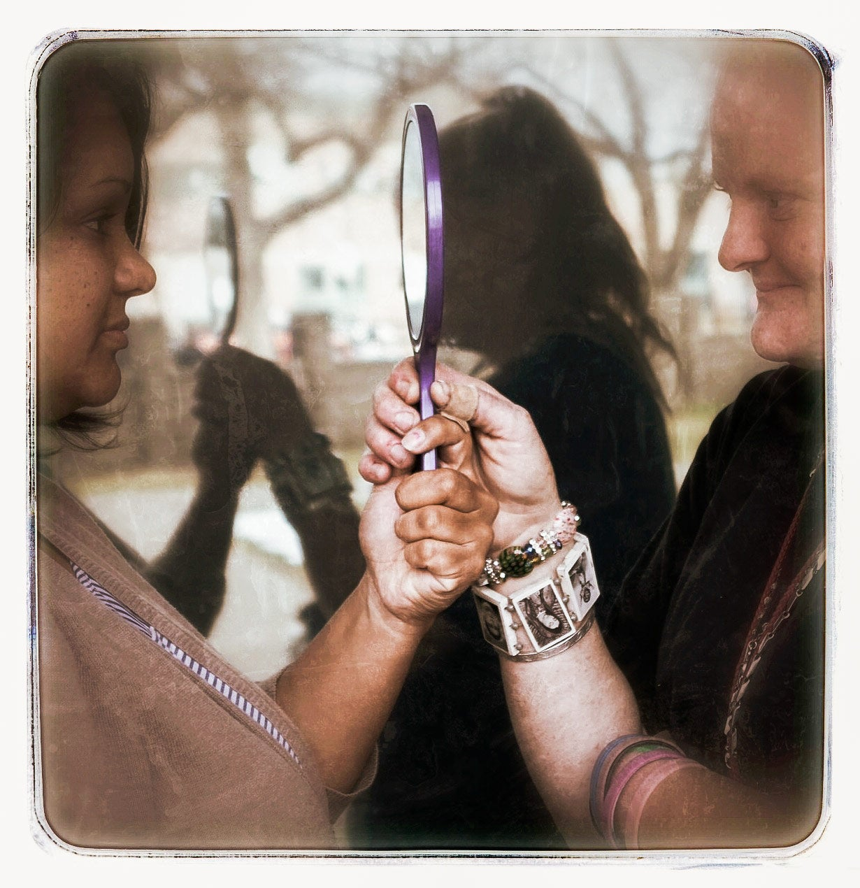 Two women hold a handheld mirror. This image appears in the book EXPOSURE: Homelessness through the lens of art & poetry.