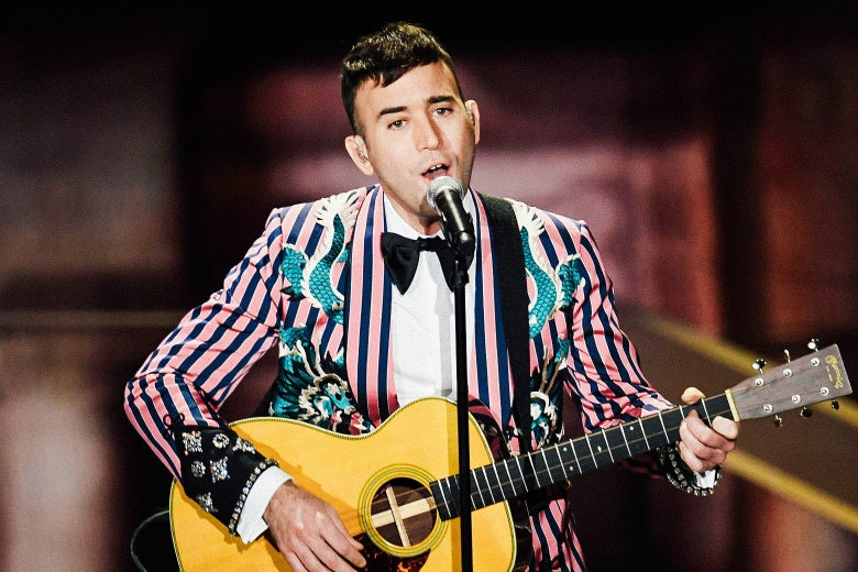 Sufjan Stevens playing guitar and singing into a microphone