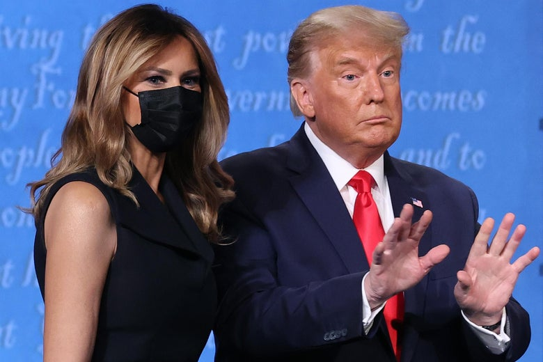 Trump holds up both his hands while standing next to Melania, who's wearing a mask, on the debate stage following the final presidential debate.
