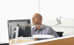 Businessman peering over computer monitor.