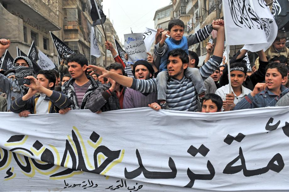 Syrian protesters wave Islamist flags as they march during an anti-regime demonstration in the northern city of Aleppo, Syria, on March 22, 2013.
