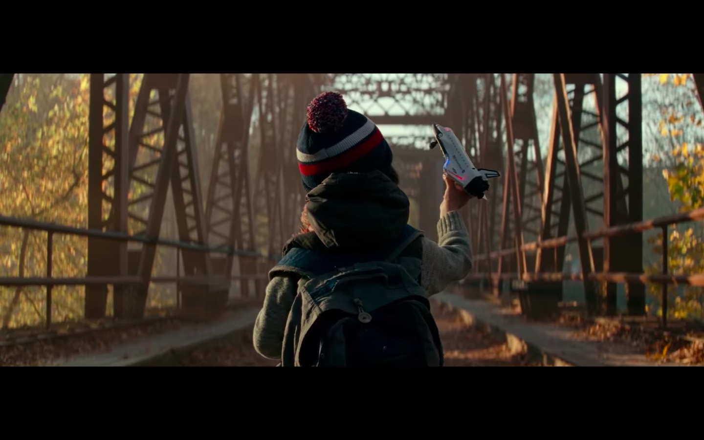 A shot of a little boy from behind. He stands in front of a bridge wearing a knit cap, vest, and backpack. His right hand is raised, and he holds a toy rocket.