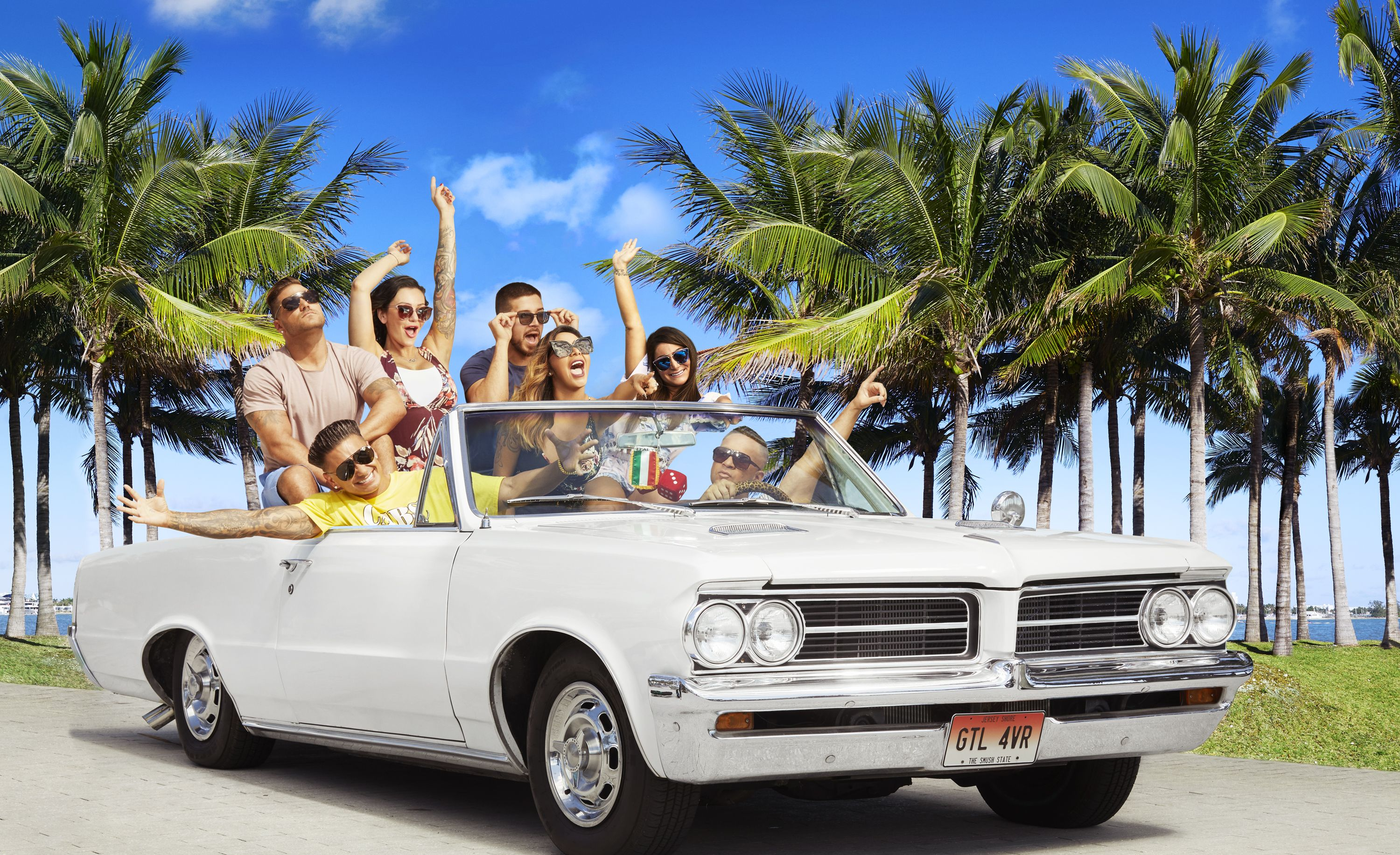 The cast of Jersey Shore Family Vacation drives down a palm tree–lined street in a white convertible.