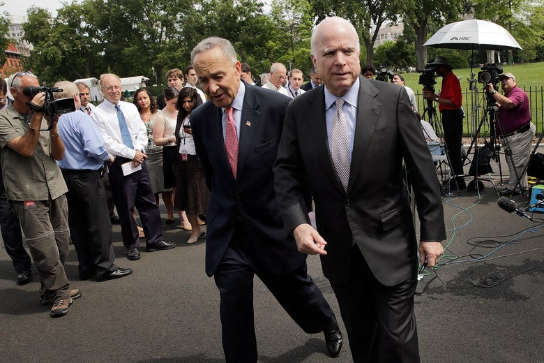 Sen. Charles Schumer (D-NY) (L) and Sen. John McCain (R-AZ) walk away from members of the press at the White House after answering questions July 11, 2013 in Washington, D.C.