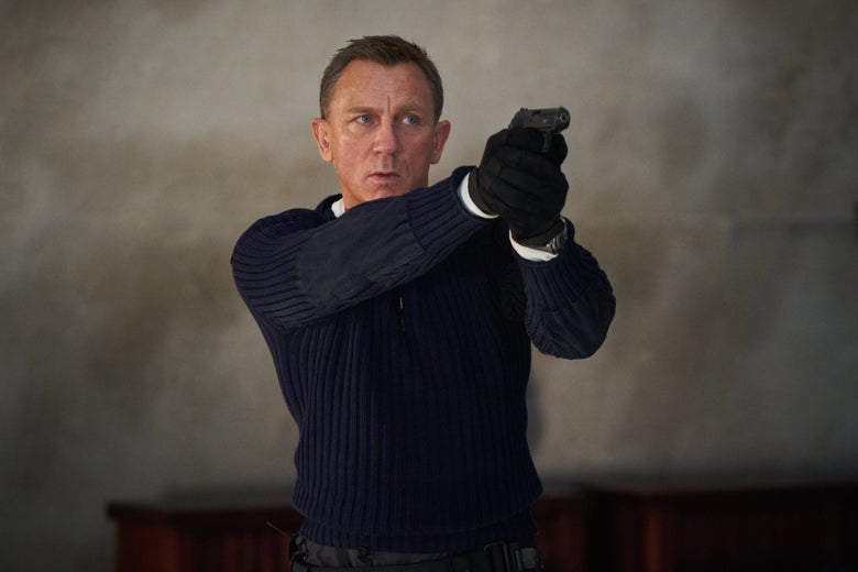 Daniel Craig wears a ribbed sweater and gloves. He points a gun.