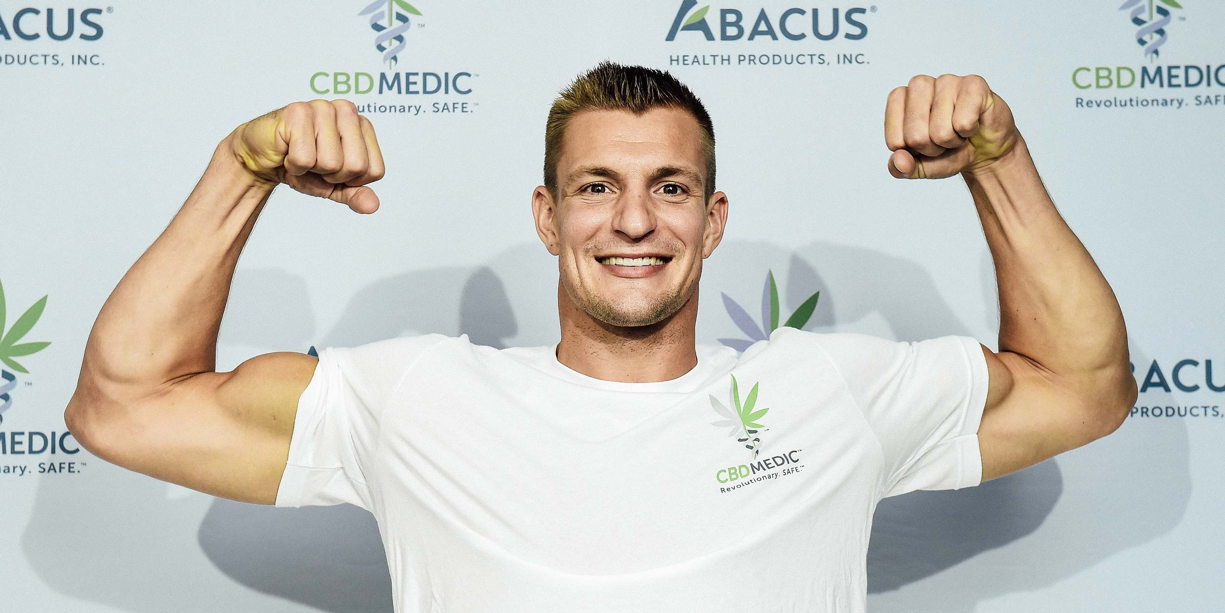 Rob Gronkowski flexing at a press conference promoting CBD.