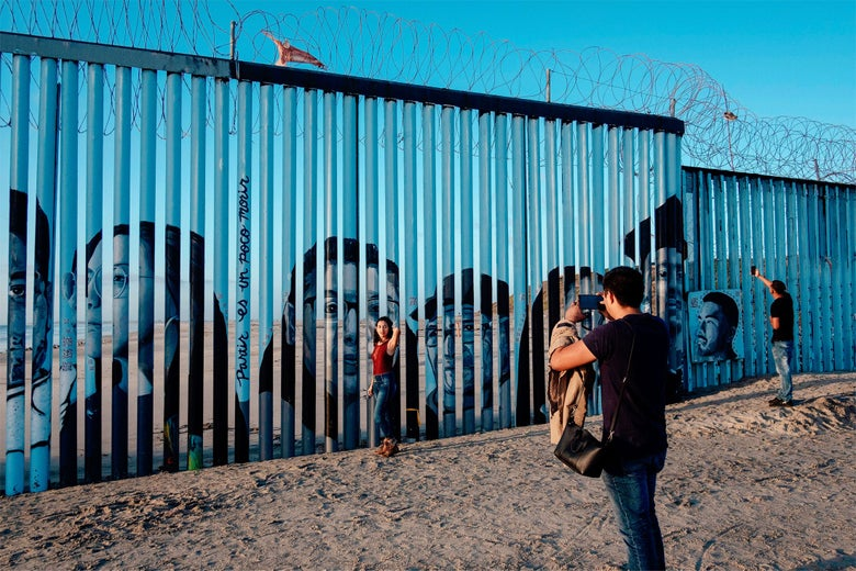 A visitor takes a picture of a woman posing in front of the US-Mexico border fence in Playas de Tijuana.