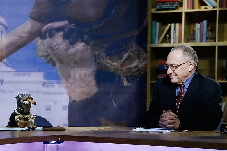 Dershowitz sits at a desk on stage next to a small dog puppet that has a cigar in its mouth.