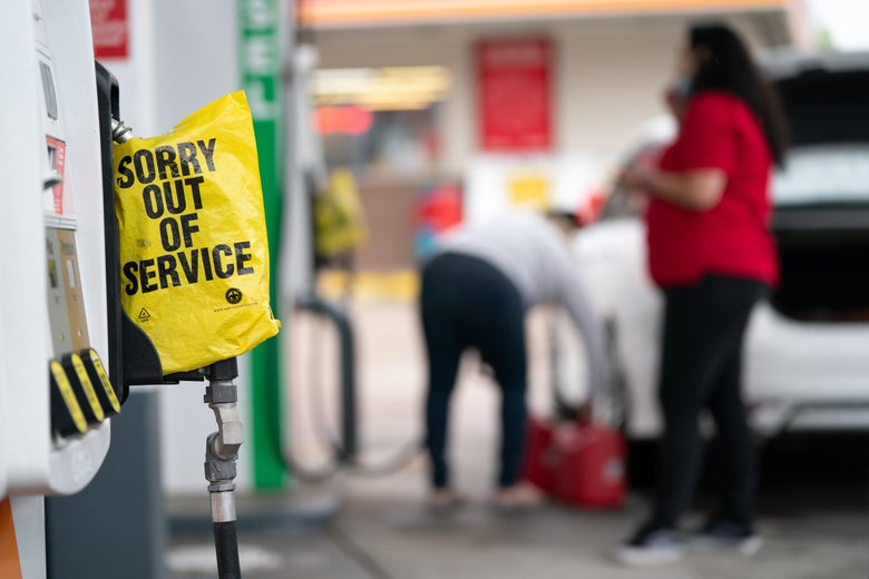 """A yellow plastic """"Sorry out of service"""" bag covers a gas pump handle."""