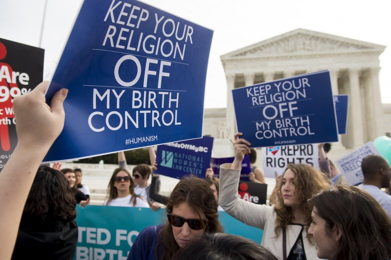 "Protesters in front of the Supreme Court hold signs that read ""Keep Your Religion OFF My Birth Control."""