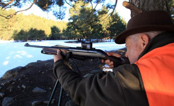 A hunter holds a rifle while a deer hunting.