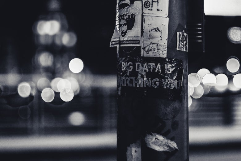 "A sticker on a lamppost says ""Big data is watching you."""