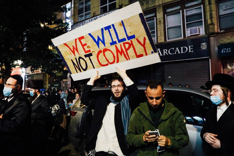 """A man holds up a sign that says, """"We will not comply."""""""