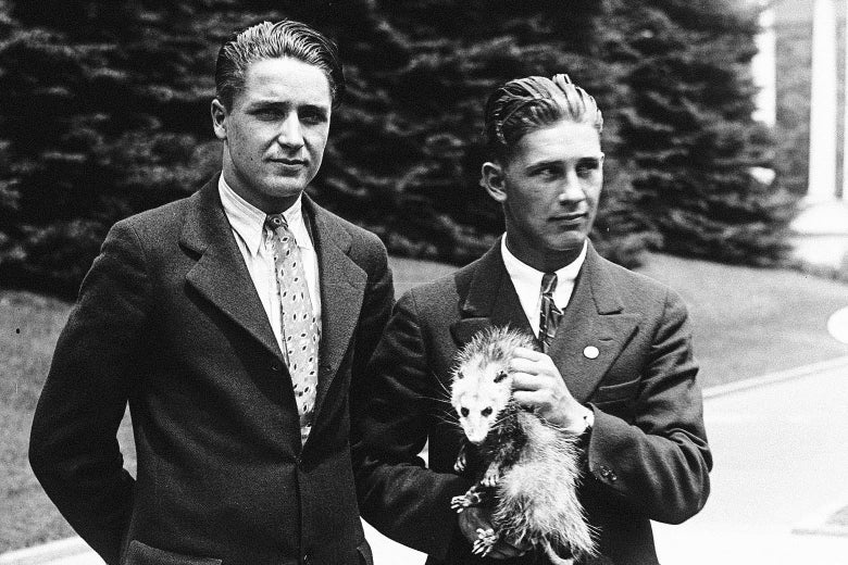"""Two suspiciously old-looking """"high school students"""" holding an angry possum in front of the White House."""