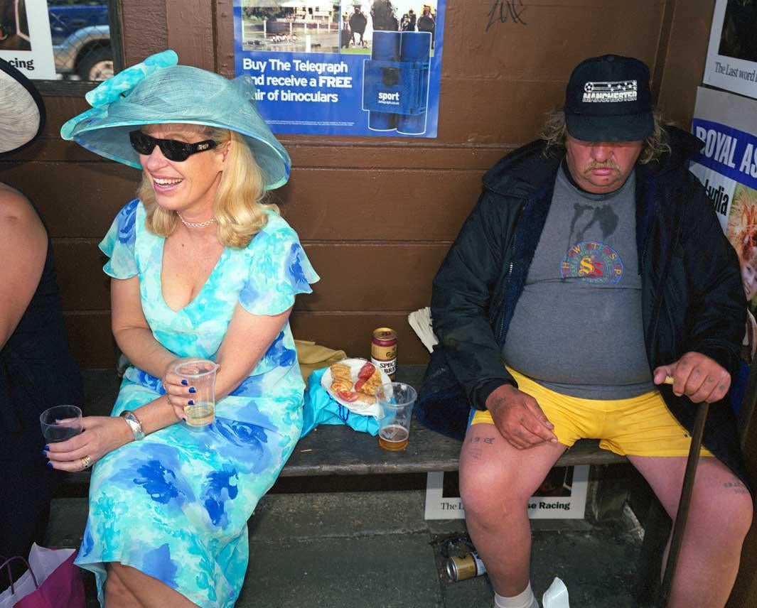 A woman drinks with friends alongside a man she doesn't know in a bus stop shelter outside Ascot race course on Ladies' Day.