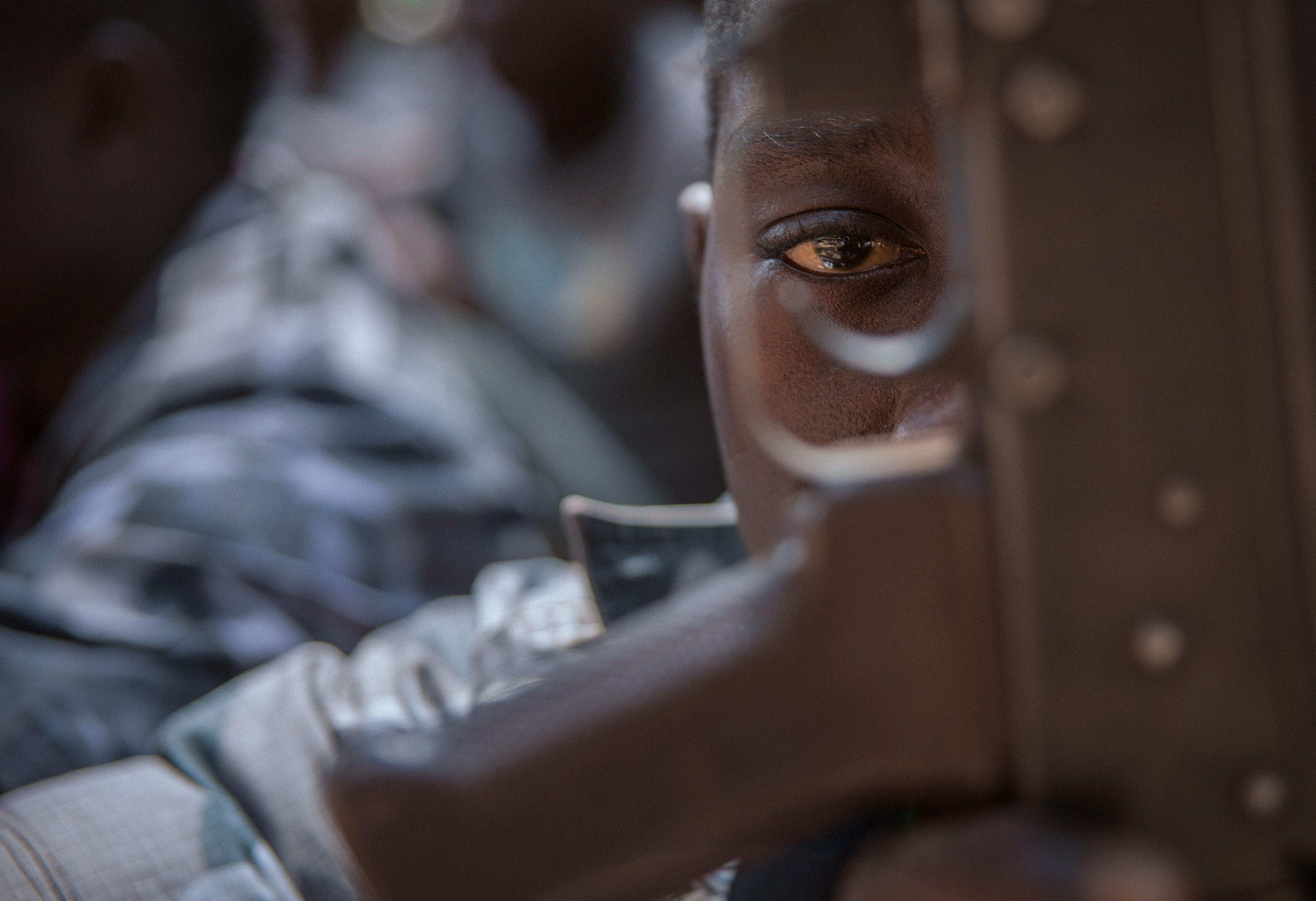 A child looks through a rifle trigger guard.