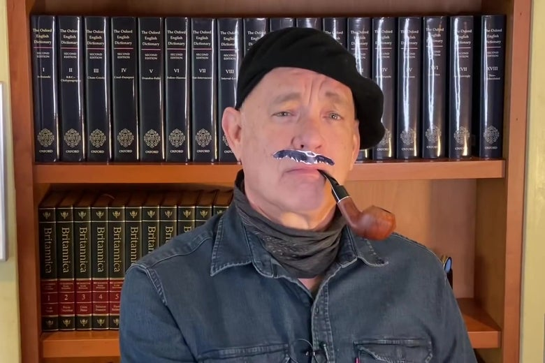 Tom Hanks, wearing a beret, fake mustache, denim shirt, and scarf, smokes a pipe in front of a bookshelf containing the first 18 volumes of the OED and an encyclopedia.