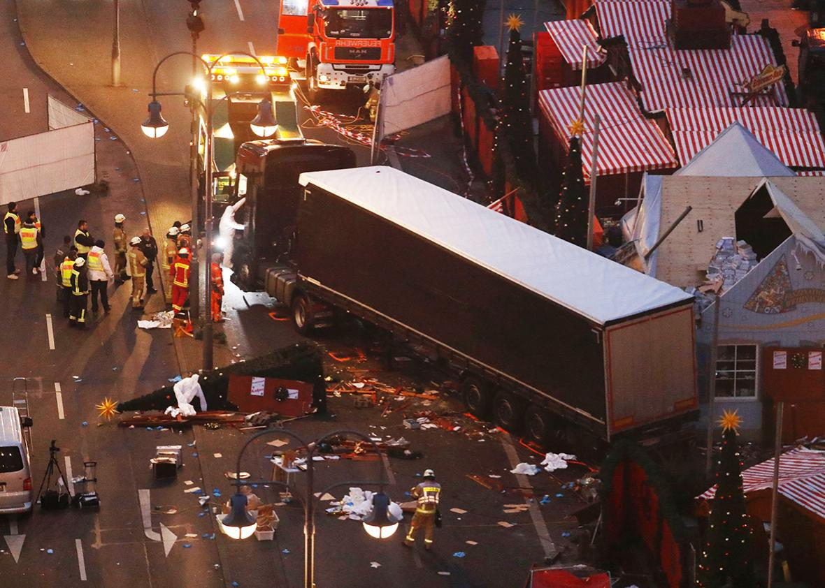 Forensic experts examine the scene around a truck that crashed into a Christmas market on December 20, 2016 in Berlin.