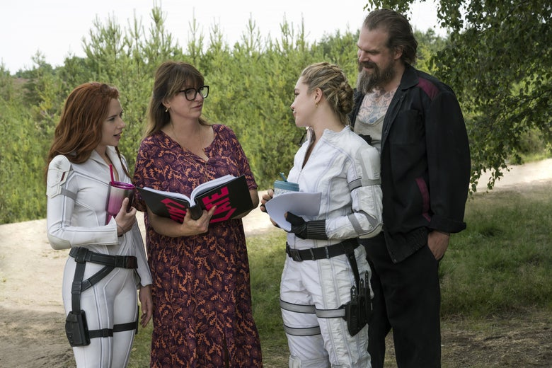 The three actors stand around the director, smiling, as she holds a large binder taped with her name on it.