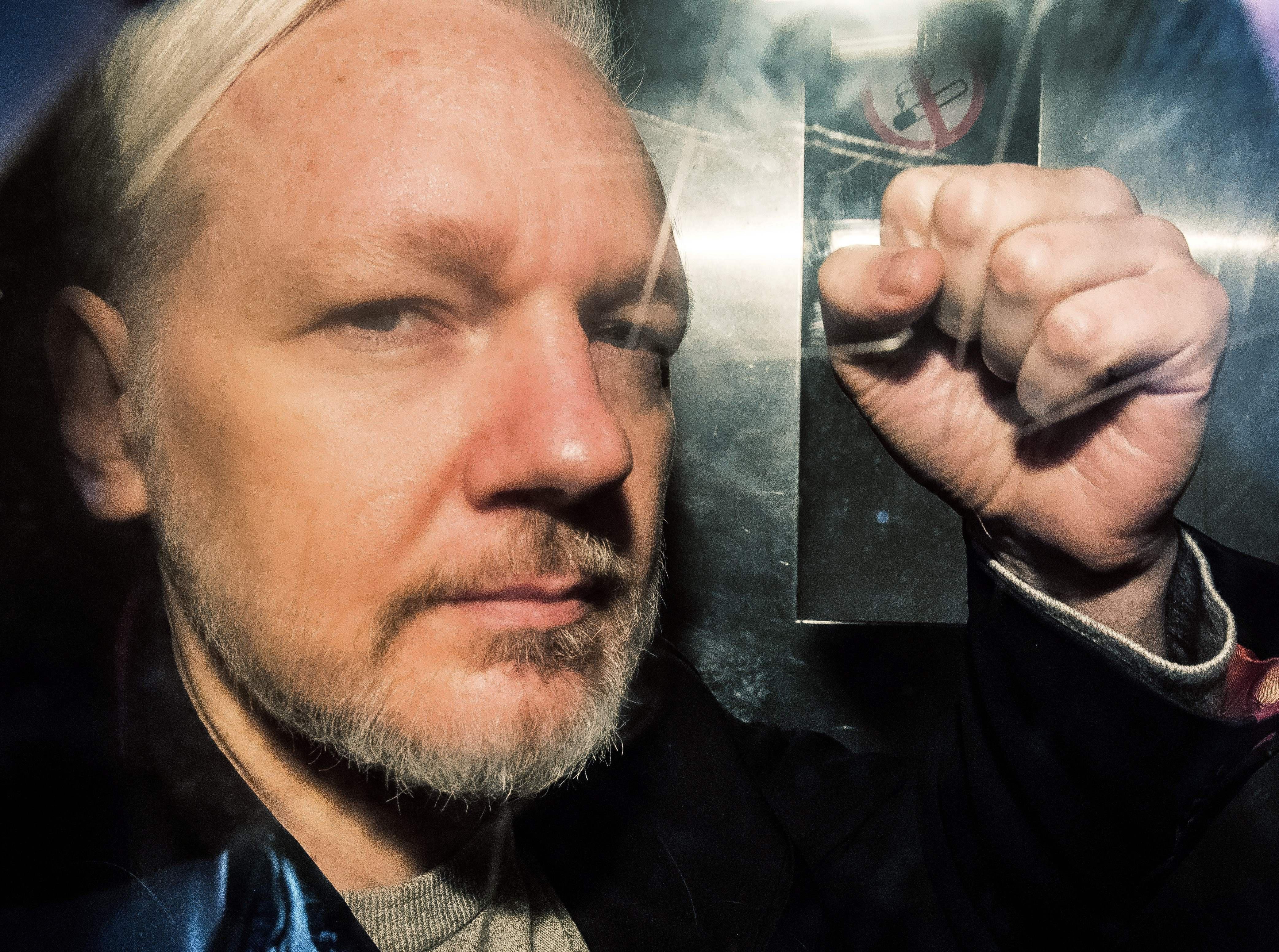 Seen through a window, Julian Assange makes a fist.