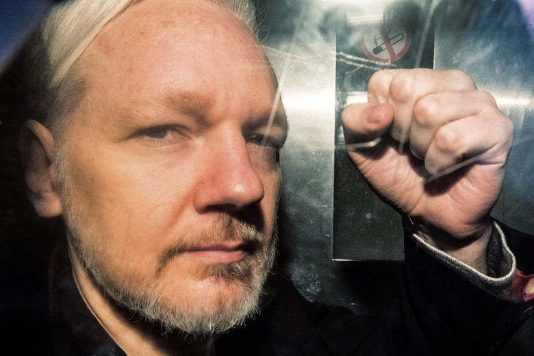 Seen through a window, Julian Assange makes a fist.