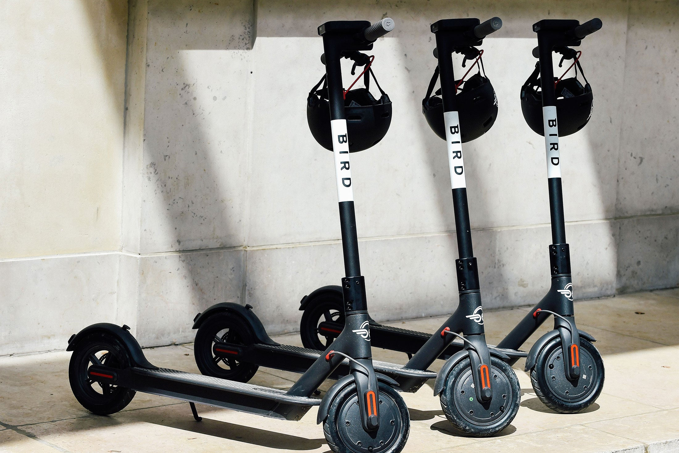 Three bird scooters with helmets hanging from the handlebars.