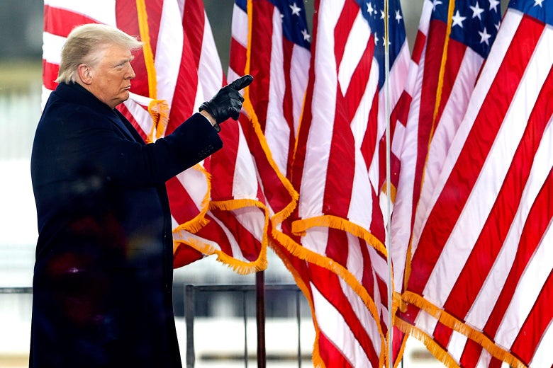 Trump stands behind bulletproof glass and in front of American flags while inciting supporters in front of the White House.