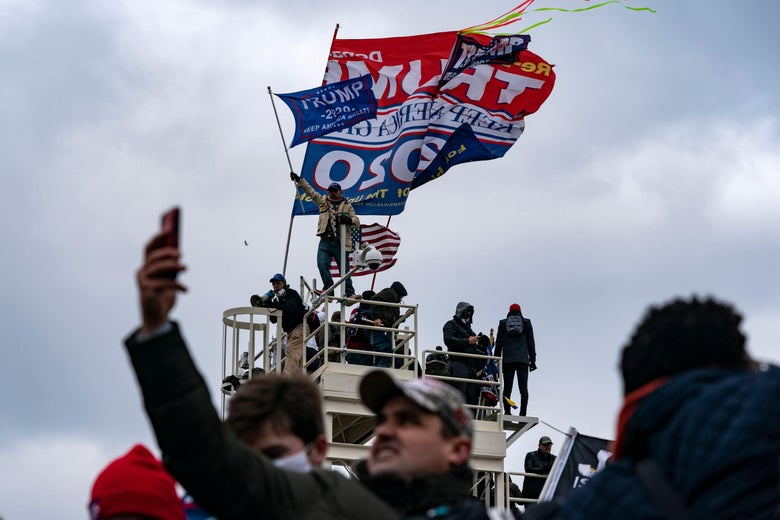 People waving Trump flags mass on top of a platform on a cloudy day. Below, a Trump supporter holds his phone up to take a photo of the chaos.