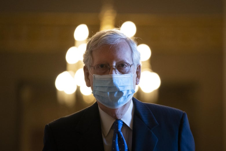 Mitch McConnell walking, wearing a mask, with a chandelier behind his head