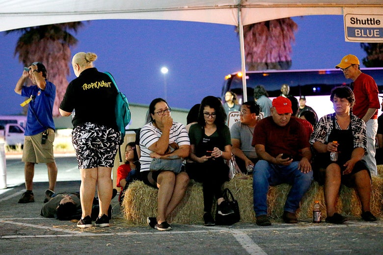 Festival attendees wait for relatives at a reunification center at Gavilan College following a shooting at the Gilroy Garlic Festival on Sunday.