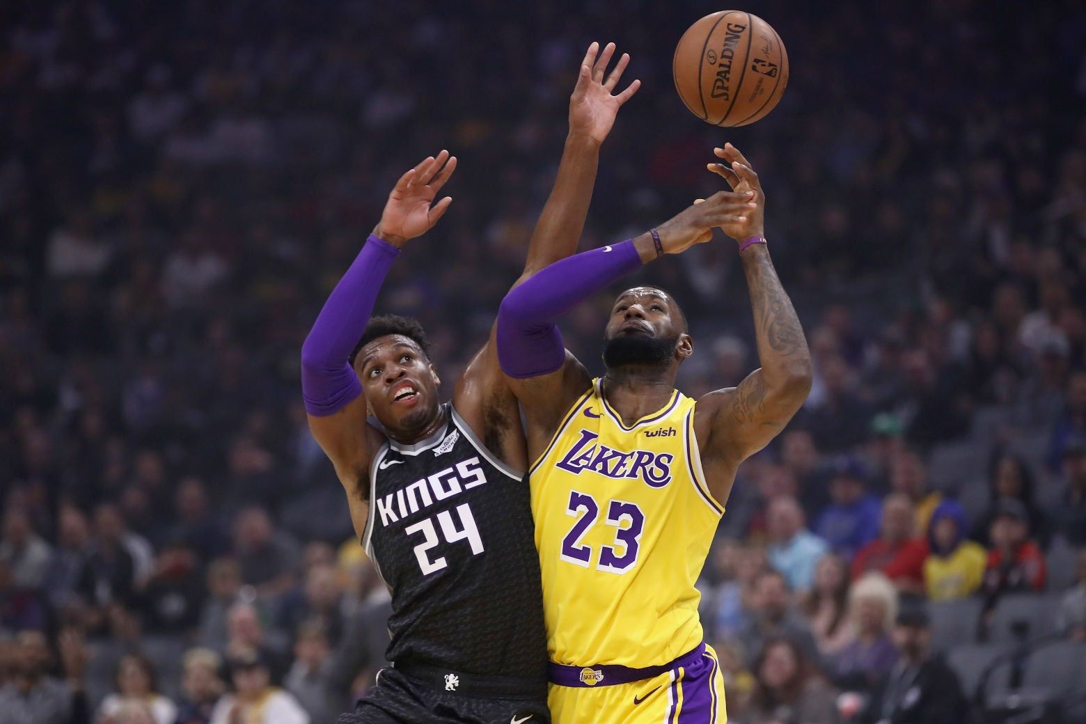 LeBron James and Buddy Hield go for the ball on Saturday at Golden 1 Center in Sacramento, California.