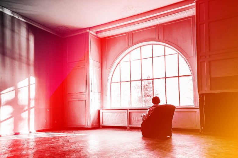 A woman sits alone in a massive room with sunlit windows.