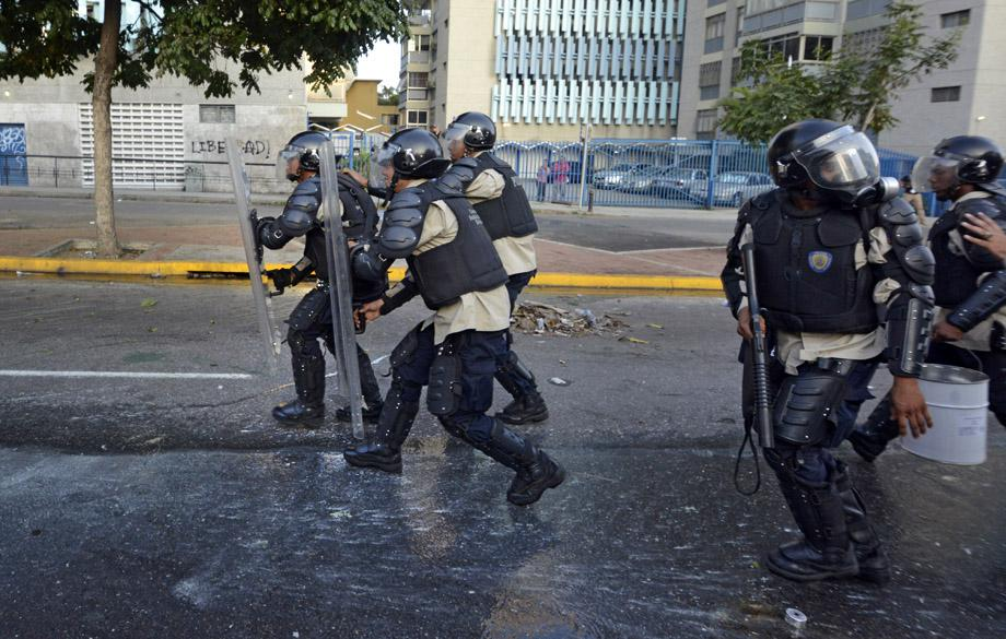 Members of the National Police clash with demonstrators during an anti-government protest, in Caracas on February 19, 2014.