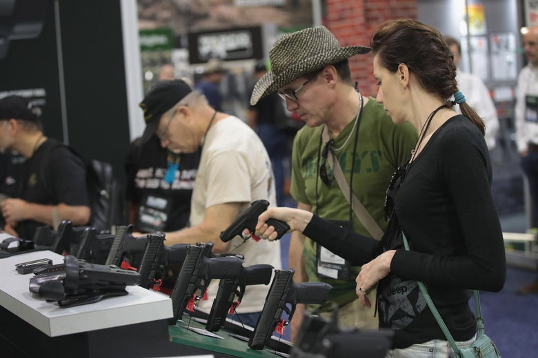 NRA members look over pistols in the Remington display at the NRA Annual exhibit.
