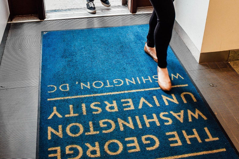 Admitted George Washington University students and their parents walk across a branded doormat as they tour the campus before deciding whether or not to enroll on April 26, 2017, in Washington.