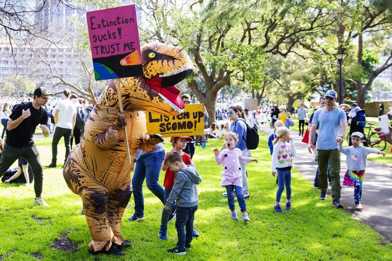"Children react as a man dressed as a dinosaur  carries a banner that says ""extinciton sucks! trust me"""