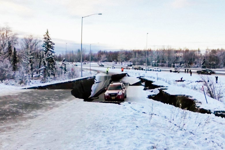 A crevasse splits a road off a snowy highway, with one car stuck in a depression
