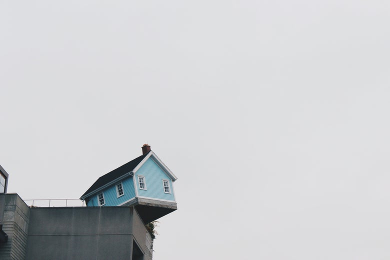 A robin's egg blue house perched on a ledge, where it is definitely not supposed to be.