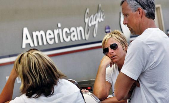 American Airlines customer rests her head on the counter.