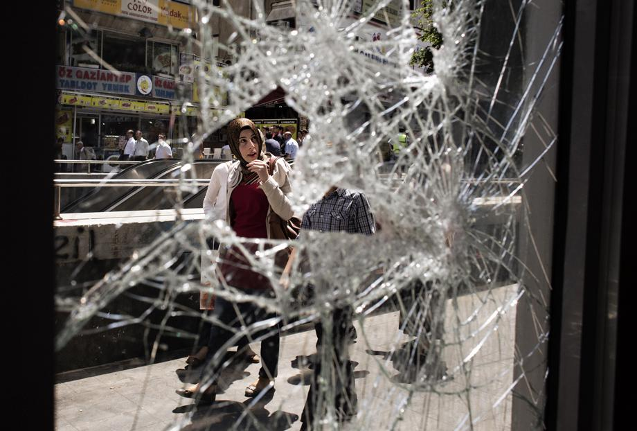 A woman looks at shattered windows as she walks past the entrance of a building damaged during previous day clashes between protesters and riot police, near the central Kizilay square in Ankara, on June 5, 2013.