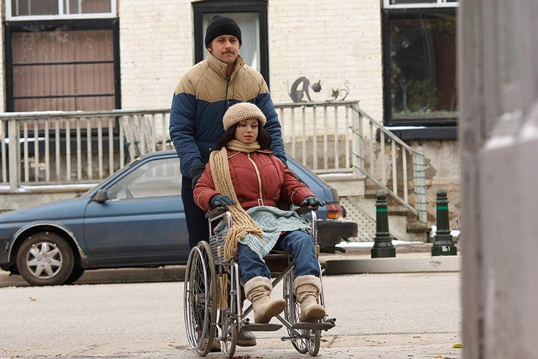 Ryan Gosling pushes a mannequin in a wheelchair.