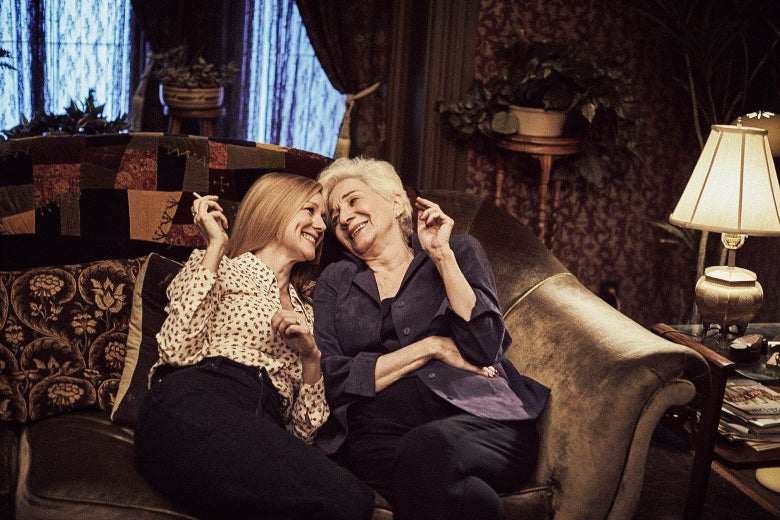 Laura Linney and Olympia Dukakis laugh while smoking cigarettes on a loveseat in this still from Tales of the City.