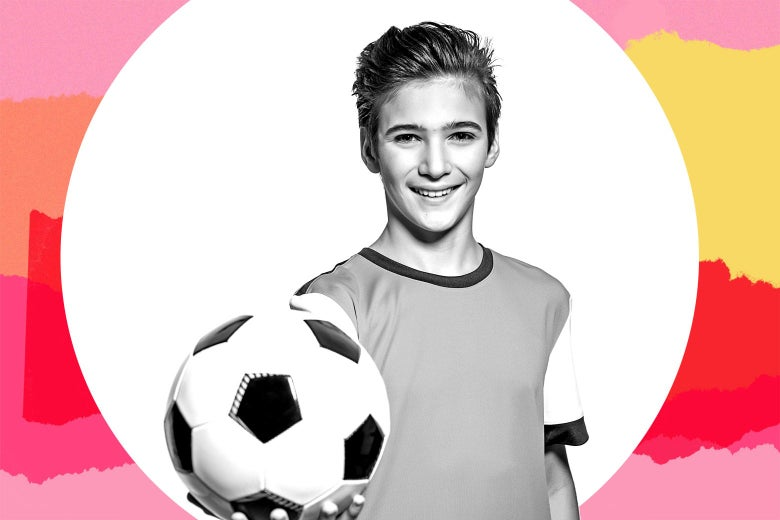 A young boy in a soccer uniform holding out a soccer ball.