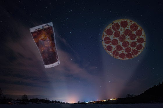 A glass of soda and a pizza in the night sky.