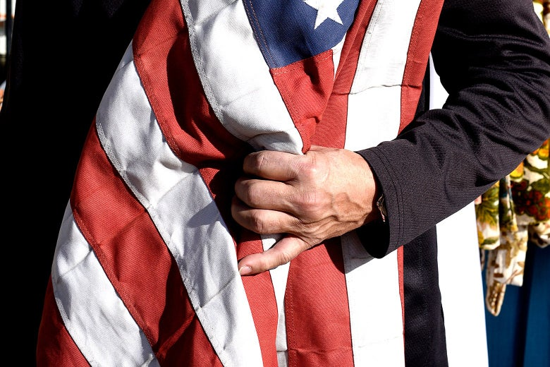 An arm holds a United States flag.